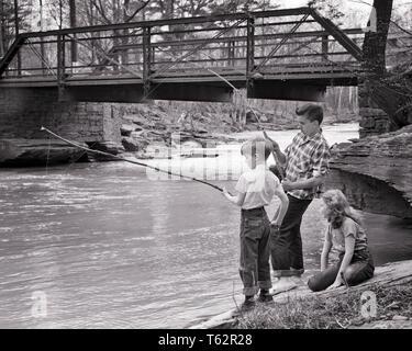 1950er Jahre junges Mädchen sitzen neben Creek von STRASSENBRÜCKE BEOBACHTEN ZWEI JUNGEN FISCHEN IN rauschenden Wasser über lange HOLZ POLEN UND STRING - eine 878 DEB001 HARS 1 JUGENDLICHE BALANCE SICHERHEIT ATHLET LIFESTYLE FRAUEN BRÜDER LÄNDLICHEN RAUM KOPIEREN FREUNDSCHAFT IN VOLLER LÄNGE STREAM MÄNNER RISIKO ATHLETISCHE GESCHWISTER VERTRAUEN SCHWESTERN B&W POLEN ABENTEUER hetzen und Aufregung Erholung durch Geschwister mit konzeptionellen NEBEN STICKS STILVOLLE DEB 001 jugendliche ENTSPANNUNG STANGEN MITEINANDER SCHWARZ UND WEISS KAUKASISCHEN ETHNIE CREEK ALTMODISCH - Stockfoto