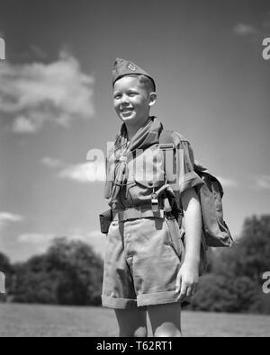 1950 lächelnde junge Teenager BOY SCOUT STEHEND AN AUFMERKSAMKEIT TRAGEN EINHEITLICHE CAP SHIRT HALSTUCH SHORTS PACK PFEIFEN IM FREIEN - b 6044 HAR 001 HARS JUVENILE GESICHTSBEHANDLUNG STIL SICHERHEIT GERNE FREUDE LIFESTYLE ZUFRIEDENHEIT SCOUT PACK LÄNDLICHEN GESUNDHEIT KOPIE RAUM MIT HALBER LÄNGE PERSONEN INSPIRATION PFADFINDER MÄNNLICHE TEENAGER AUSDRÜCKE B&W ERFOLG GLÜCK FRÖHLICHEN ABENTEUER STÄRKE MUT AUFMERKSAMKEIT WAHL WISSEN FÜHRUNG FREIZEIT STOLZ HALSTUCH am Lächeln PFADFINDER THRIFTY KONZEPTIONELLE zuvorkommend freundlich hilfsbereit FREUDIGE ART REVERENT STILVOLLE TEENAGED VERTRAUENSVOLLE ZUSAMMENARBEIT KREATIVITÄT Wachstum von Jungfischen - Stockfoto