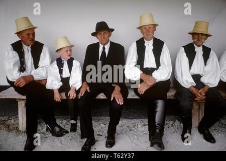 1980 s Gruppe älterer Männer mit kleiner Junge sitzt AUF DER BANK ALLE IN DER LOKALEN TRADITION KOSTÜME SIC RUMÄNIEN - kr 55318 PZS001 HARS KOPIE RAUM FREUNDSCHAFT halber Länge PERSONEN TRADITIONELLE AUSLÄNDISCHE FESTIVAL MÄNNER ÄLTERER Mann älterer Erwachsener EUROPA AUGENKONTAKT OLDSTERS ALTEM EUROPÄISCHEN UND TRADITION STOLZ, jungen und alten örtlichen Ältesten VERBINDUNG NATIVE KOSTÜM STILVOLLE ÄLTERER MANN REISEN EUROPA JUGENDLICHE MITEINANDER YOUNGSTER KAUKASISCHEN ETHNIE NATIVE DRESS - Stockfoto
