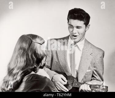 1950s Paar Mann in Anzug und Krawatte singen spielen UKULELE FÜR FRAU AUS GESEHEN HINTER-m 1825 CLE003 HARS DAMEN PERSONEN INSPIRATION MÄNNER UNTERHALTUNG B&W Anzug und Krawatte GLÜCK HOHEN WINKEL UND FRISUR SONG VOCAL RÜCKANSICHT ENTERTAINER MUSIKINSTRUMENT VERBINDUNG VOCALISE KONZEPTIONELLE GESANG lange Haare SONGS STILVOLL UKULELE RÜCKANSICHT KREATIVITÄT MITEINANDER junger erwachsener Mann junger Erwachsener FRAU SCHWARZ UND WEISS KAUKASISCHEN ETHNIE ALTMODISCH - Stockfoto