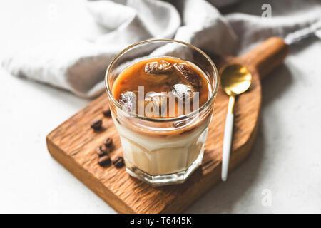 Eis Kaffee mit Sahne in einem Glas auf Holzbrett. Kalter Kaffee brühen - Stockfoto