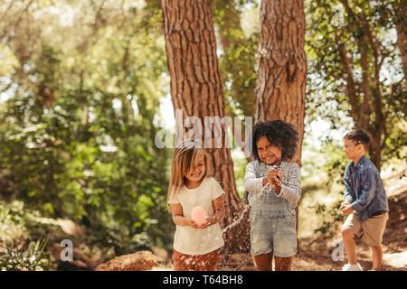 Mädchen schließt die Augen, während platzen Wasserbomben. Wassertropfen fliegen durch die Luft, und die Kinder haben Spaß im Park.