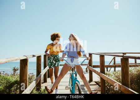 Junge Frau Reiten Fahrrad am Boardwalk mit Freund durch Ausführen. Multi-ethnischen Mädchen Spaß mit dem Fahrrad am Meer Strandpromenade. - Stockfoto