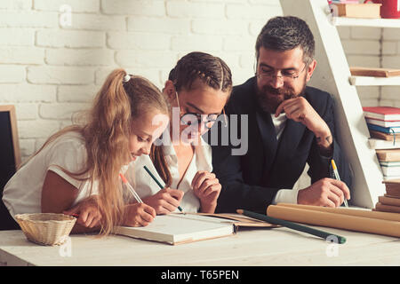 Vater und Tochter schreiben weiß Heimunterricht. Vater hilft den Kindern, sich zu Hause zu studieren. - Stockfoto