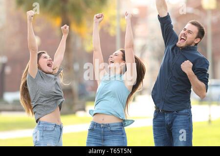 Vorderansicht Portrait von 3 fröhliche Freunde springen Erfolg feiern in einem Park - Stockfoto