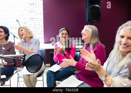 Gerne Frauen Chor mit Noten singen und klatschen in Music Recording Studio - Stockfoto
