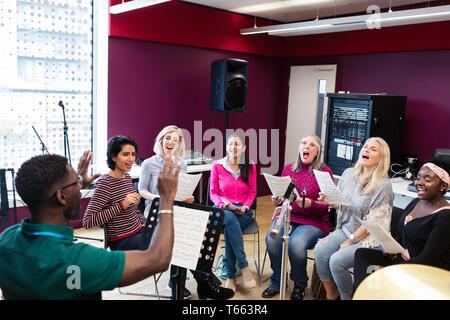 Männliche Leiter der führenden Frauen Chor mit Noten singen in Music Recording Studio - Stockfoto