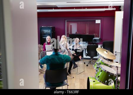 Männliche Leiter führenden Frauen singen in Music Recording Studio - Stockfoto