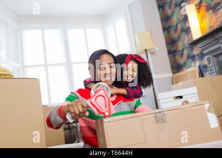 Liebevolle Mutter und Tochter Verpackung, Umzug - Stockfoto