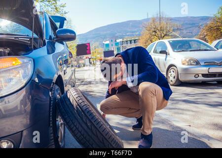 Wütend Geschäftsmann versucht, seine Reifen mit einem Steckschlüssel zu ändern, während Sie geduckt Neben seinem Auto. - Stockfoto