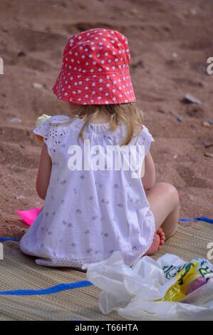Kleines blondes Mädchen am Strand mit roten Hut - Stockfoto
