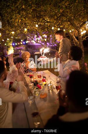 Freunde feiern Geburtstag mit Wunderkerzen Kuchen im Garden Party - Stockfoto