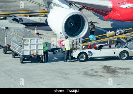 Bali, Denpasar, 2018-05-01: Mann legt das Gepäck vom Trailer zum Förderband auf der Ebene. Entladen von Gepäck aus dem Flugzeug. - Stockfoto