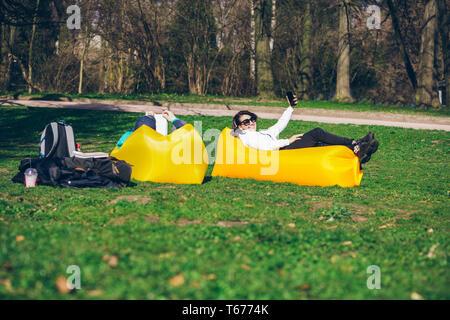 Paar Festlegung auf Gelb aufblasbare Matratze im City Park. Lesen Buch. Bei Einnahme von selfie. Freizeit - Stockfoto