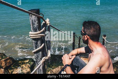 Kaukasischen jungen Mann ohne Hemd und Sonnenbrille sitzen auf der Treppe am Strand in der Nähe des Meeres - Stockfoto