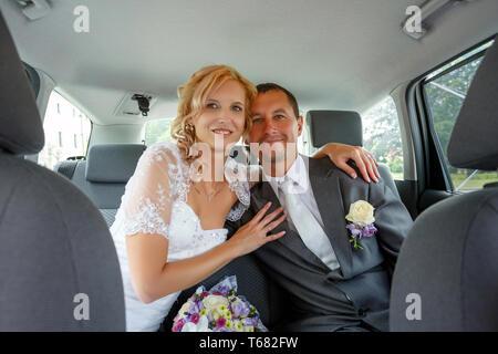 Schönes junges Hochzeitspaar im Auto.