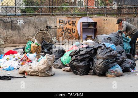 Kathmandu, Nepal - April 20th, 2019 - Garbage Collector Sortieren durch Berge von Müll in den frühen Morgenstunden auf der Straße. - Stockfoto