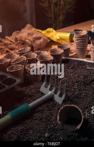 Der ökologische Landbau Rechen und die Töpfe in den Boden für die Aussaat und Anpflanzung von homegrown Saison produzieren bereit im Frühjahr - Stockfoto
