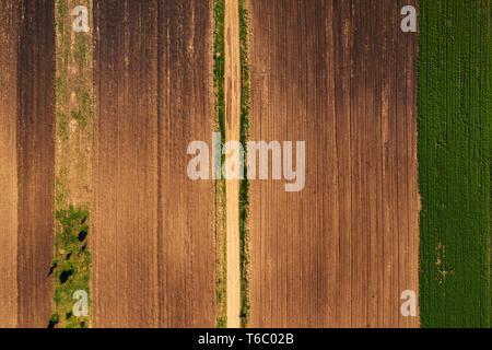 Luftaufnahme der Schmutz der Straße durch landwirtschaftliche Feld von oben nach unten Blick von Drone pov, abstrakte Natur Hintergrund - Stockfoto