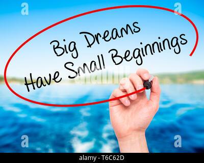 Mann Hand schreiben Große Träume haben Kleine Anfänge mit schwarzem Marker auf visuelle Bildschirm - Stockfoto