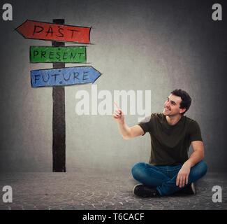 Junger Mann saß auf dem Boden zeigen Zeigefinger am Wegweiser Pfeile zeigt Vergangenheit, Gegenwart und Zukunft. Verloren in der Zeit bunte Schild, Schicksal evoluti - Stockfoto