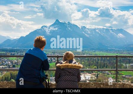 Kinder reisen, Rückansicht der Kinder auf eine alpine Bergwelt von einer Aussichtsterrasse in Salzburg Burg (Festung), Österreich. Stockfoto