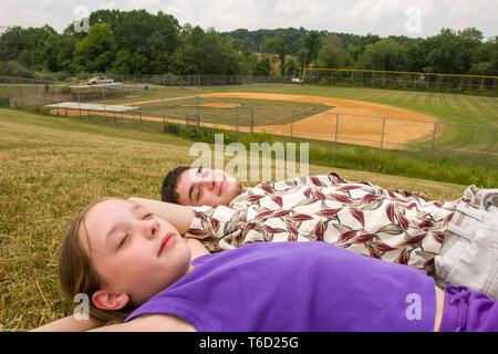 Bruder und Schwester liegend im Gras und Entspannen vor der Baseball Spiel neben einem Baseballfeld. - Stockfoto