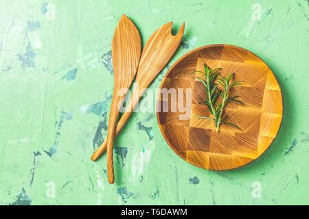 Kochlöffel für Salat und hölzerne Platte über grüne konkrete Textur Hintergrund, gesunde Ernährung Konzept, Ansicht von oben, kopieren Sie Text. - Stockfoto