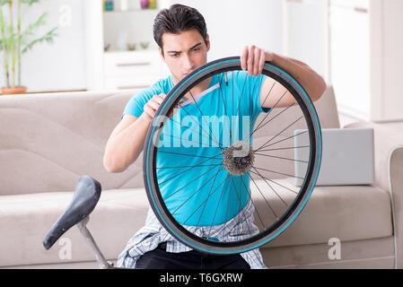 Junger Mann Fahrrad zu Hause reparieren - Stockfoto