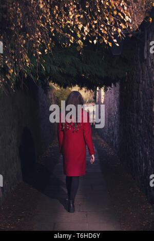 Frau hinunter eine schmale dunkle Gasse, die alle auf ihre eigene - Stockfoto