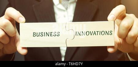 Geschäftsmann sammelt Rätsel mit den Worten Business und Innovationen. Innovative Ideen für kleine Unternehmen. Technische, technologische und strategische in - Stockfoto