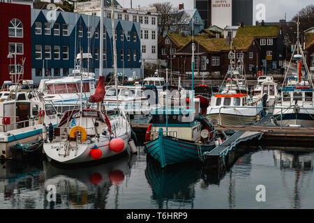 Little Angel- und Segelboote im Hafen von Tórshavn vor typisch Färöischen Holz- und mit Gras bewachsene Häuser (Färöer Inseln, Europa) - Stockfoto