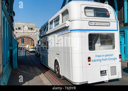 LONDON, Großbritannien - 1 April, 2019: Seltene weiße Google Bus fahren über die Tower Bridge - Stockfoto