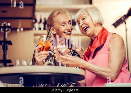 Strahlend helle Frauen in super Stimmung beim Trinken - Stockfoto