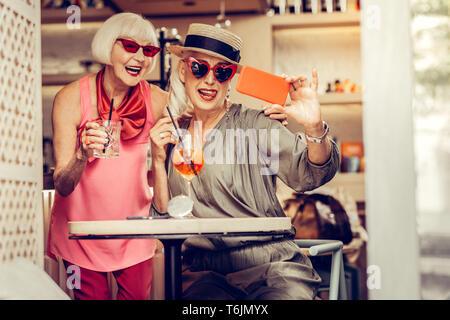 Entschlossenen fröhliche ältere Frauen mit hellen stilvollen Outfits - Stockfoto