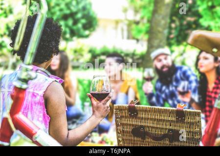 Eine Gruppe von Freunden ein Picknick im Garten Outdoor - Glückliche junge Menschen, ein lustiges Treffen mit Essen und Rotwein sitzen auf Gras in einem Park - Stockfoto