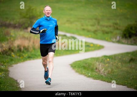 Älterer Mann in 50 s die Ausübung und Halten, indem Sie in einem Park anbringen - Stockfoto
