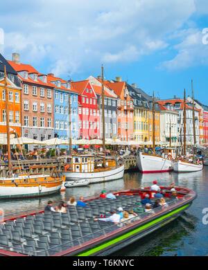 Tour segeln von Canal mit alten Segelboote im Hafen Nyhavn, Personen zu Fuß am sonnigen Ufer und Sitzen in Cafes und Restaurants, Kopenhagen, D - Stockfoto