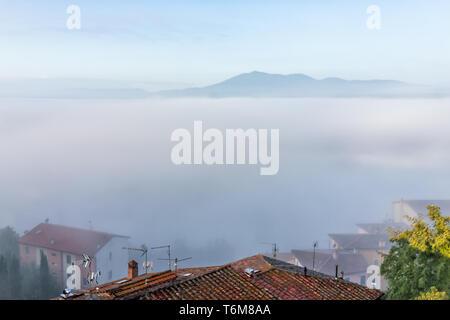 Chiusi Scalo Nebel Nebel Sonnenaufgang auf dem Dach Häuser Gebäude in Italien nahe der Toskana mit weichen Wolken bedeckt, Stadt im Sommer - Stockfoto