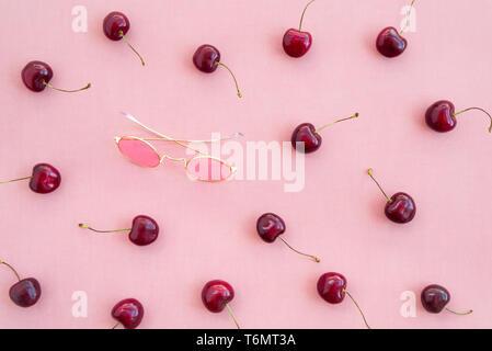 Süßkirschen und runde rosa Sonnenbrille auf Leinwand Hintergrund. - Stockfoto