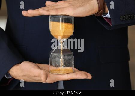 Mann mit Sanduhr, Nahaufnahme. Zeit-management Konzept - Stockfoto