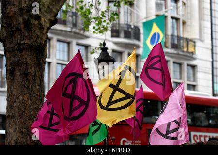 Aussterben Rebellion Fahnen und brasilianische Flagge im Hintergrund sind während des Protestes außerhalb der Brasilianischen Botschaft in London gesehen. Aussterben Rebellion Aktivisten versammelten sich vor Brasilien Botschaft in London die Artenvielfalt der Amazonas Regenwald und Nachfrage der Regenwald Ausbeutung zu beenden und sie zu schützen, zu feiern. - Stockfoto