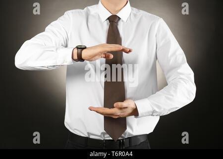Junge Unternehmer halten etwas auf farbigen Hintergrund - Stockfoto