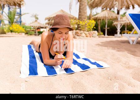 Lächelnde junge Frau liegt auf gestreiftes Handtuch auf den Sand am Strand und Anwendung von Sonnencreme auf ihre Hand. - Stockfoto