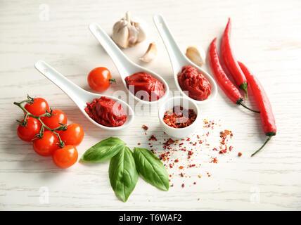 Köstliche rote Soße in Keramik Löffel und Zutaten auf Tisch - Stockfoto