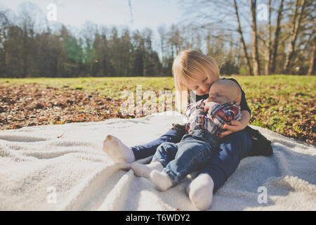 Schwester hält ihr Bruder während auf picknickdecke draußen im Park Stockfoto