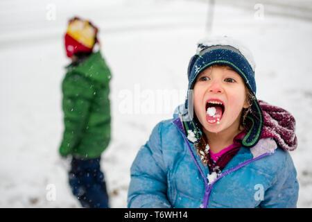 Ein kleines Mädchen in einem Fuzzy hat frisst Schnee mit Bruder im Hintergrund - Stockfoto
