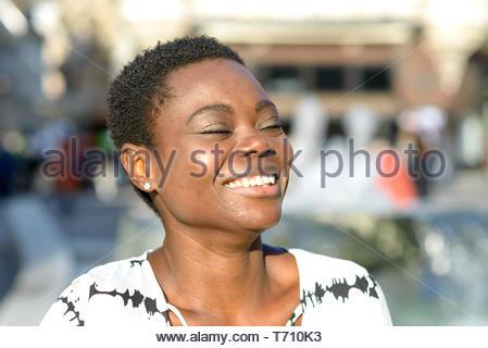 Lebendige junge afrikanische Frau mit einem strahlenden Lächeln - Stockfoto