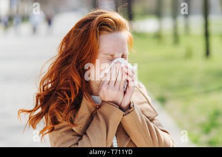 Junge Frau leidet unter Heuschnupfen Pollen Allergie im Frühjahr ihre Nase weht auf ein Gewebe im Freien in einem Park - Stockfoto