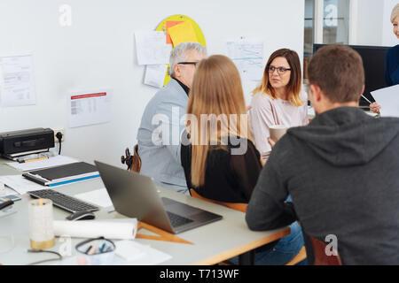 Mitarbeiter in einem Brainstorming im Büro sitzen in einem Kreis in einer Diskussion mit einem Blick über einen Schreibtisch, eine Frau in der Rückseite von t - Stockfoto